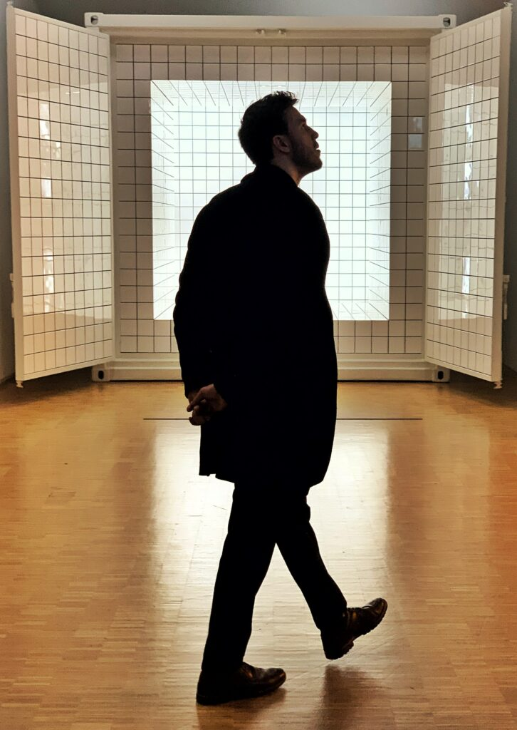 Man in a long black coat stands relectivelywith hands behind his back as he stares out into the distance