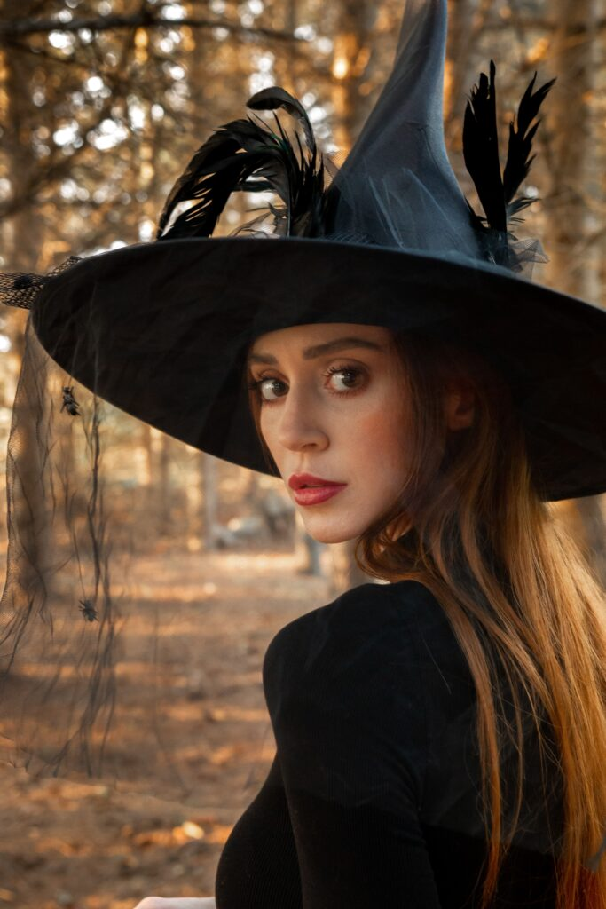 Woman dressed as a witch looks over her shoulder towards the camera