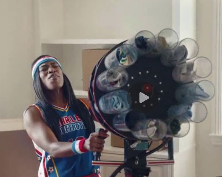 Female Harlem Globetrotter prepares to fire folded clothing across a rooms