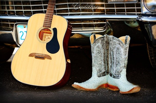 Guitar, white cowboy boots displayed in front of the grill of a car